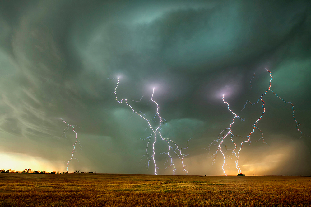 Green and black clouds. Multiple lightning bolts strike the ground over the Great Plains.