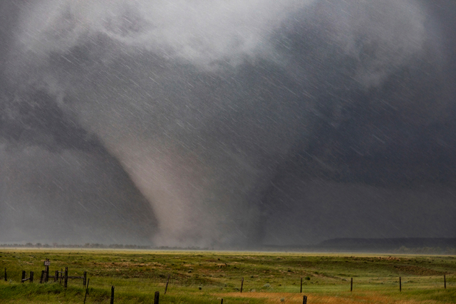 a monster wedge-shaped tornado surrounded by hail