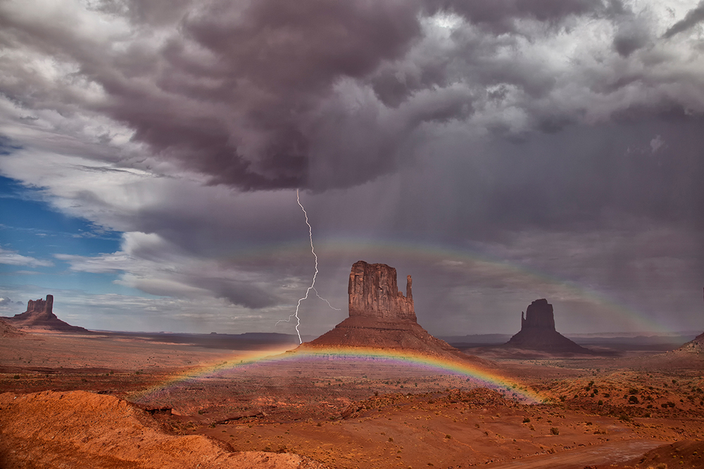 A storm over Monument Valley with a lightning bolt and a double rainbow