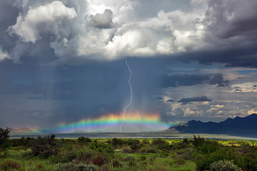 A storm over the high plains of New Mexico shadows a mountain range. A lightning bolt strikes through a rainbow.