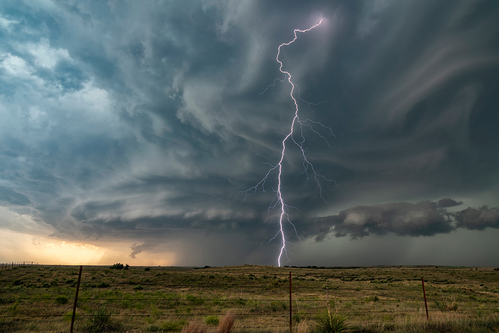 A single lightning bolt hits the ground in front of a supercell over the prairie.