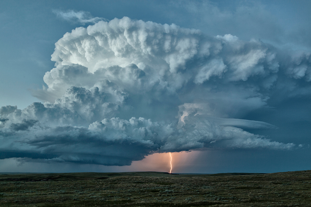 A massive supercell storm over a single lightning bolt.